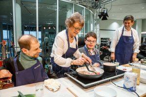 Constantin Grosch und drei weitere Personen kochen etwas auf der Bühne an einer Herdplatte