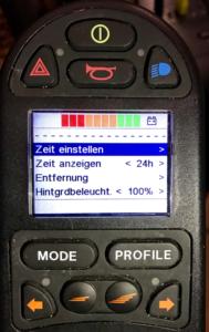 LCD-Display in einer Rollstuhl-Steuerung. Auf dem Display ist ein Menü angezeigt: Zeit einstellen. Zeit anzeigen. Entfernung. Hintergrundbeleuchtung.