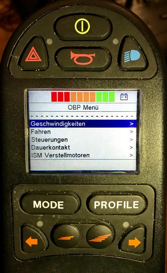 LCD-Display in einer Rollstuhl-Steuerung. Auf dem Display ist ein Menü angezeigt: Geschwindigkeiten. Fahren. Steuerungen. Dauerkontakt. ISM Verstellmotoren.